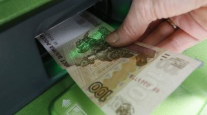 A woman inserts a 100-rouble banknote into an ATM bank machine at a branch of Sberbank in Krasnoyarsk
