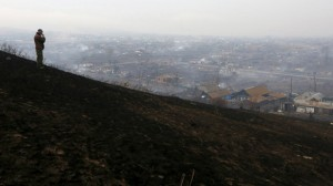 Man looks downhill at the settlement of Shyra, damaged by recent wildfires, in Khakassia region