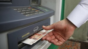 A man uses a cash dispenser to receive roubles in central Moscow, September 2, 2014. Russian assets fell on Monday, with the rouble hitting a fresh record low against the dollar after Europe and the United States accused Russia of direct military involvement in Ukraine.   REUTERS/Maxim Zmeyev (RUSSIA - Tags: BUSINESS POLITICS CIVIL UNREST CONFLICT)