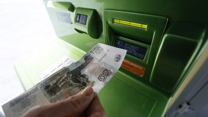 A woman inserts a 50-rouble banknote into an ATM bank machine at a branch of Sberbank in Krasnoyarsk, Siberia, January 27, 2015. Russia's rouble strengthened by over 1 percent against both the dollar and euro in early trade on Tuesday, bouncing back after taking a sharp hit late on Monday, when ratings agency S&P downgraded Russia's sovereign credit rating to 'junk'. REUTERS/Ilya Naymushin (RUSSIA - Tags: BUSINESS)