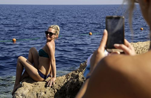 Russian tourists make a beach side photos by the Red Sea at a resort where many stranded tourists are waiting for evacuation, in Sharm el-Sheikh, south Sinai, Egypt, Saturday, Nov. 7, 2015. Egypt's Foreign Minister Sameh Shoukry complained on Saturday that Western governments had not sufficiently helped Egypt in its war on terrorism and had not shared relevant intelligence with Cairo regarding the downed Russian airplane that crashed last week in the Sinai, killing 224 people. (AP Photo/Thomas Hartwell)