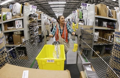 Theresa White fills orders at the Amazon fulfillment center in Lebanon, Tenn. on Monday, Dec. 1, 2014. Retailers rolled out discounts and free shipping deals on Cyber Monday, with millions of Americans expected to log on and shop on their work computers, laptops and tablets after the busy holiday shopping weekend. (AP Photo/Mark Humphrey)