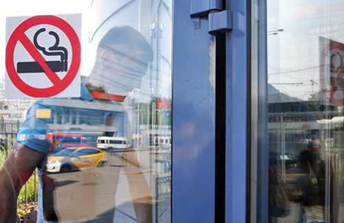 "ITAR-TASS: MOSCOW, RUSSIA. JUNE 1, 2014. A young man walks past a No Smoking sign at the entrance to a building. Starting from 1 June 2014, the second part of Russia's new anti smoking legislation comes into force: a full ban on smoking at bars, restaurants, long-distance trains, dormitories, and hotels. (Photo ITAR-TASS / Sergei Fadeichev)  –†–Њ—Б—Б–Є—П. –Ь–Њ—Б–Ї–≤–∞. 1 –Є—О–љ—П. –Ч–љ–∞–Ї –Њ –Ј–∞–њ—А–µ—В–µ –Ї—Г—А–µ–љ–Є—П –љ–∞ –і–≤–µ—А–Є –Ј–і–∞–љ–Є—П. –° 1 –Є—О–љ—П 2014 –≥–Њ–і–∞ –≤—Б—В—Г–њ–∞–µ—В –≤ —Б–Є–ї—Г –≤—В–Њ—А–∞—П —З–∞—Б—В—М ""–∞–љ—В–Є—В–∞–±–∞—З–љ–Њ–≥–Њ"" –Ј–∞–Ї–Њ–љ–∞: –Ј–∞–њ—А–µ—Й–µ–љ–Њ –Ї—Г—А–µ–љ–Є–µ –≤ –±–∞—А–∞—Е, —А–µ—Б—В–Њ—А–∞–љ–∞—Е, –њ–Њ–µ–Ј–і–∞—Е –і–∞–ї—М–љ–µ–≥–Њ —Б–ї–µ–і–Њ–≤–∞–љ–Є—П, –Њ–±—Й–µ–ґ–Є—В–Є—П—Е –Є –≥–Њ—Б—В–Є–љ–Є—Ж–∞—Е. –§–Њ—В–Њ –Ш–Ґ–Р–†-–Ґ–Р–°–°/ –°–µ—А–≥–µ–є –§–∞–і–µ–Є—З–µ–≤"