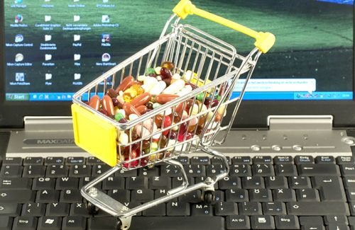 Shopping cart with medicine on keyboard of notebook / pills, tablets