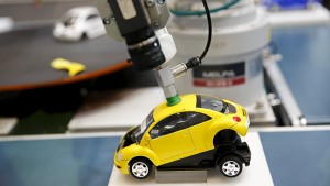 "A robotic arm by Mitsubishi Electric assembles a toy car at the System Control Fair SCF 2015 in Tokyo, Japan in this December 2, 2015 file photo. Japan is expected to release manufacturing PMI data this week. REUTERS/Thomas Peter/Files GLOBAL BUSINESS WEEK AHEAD PACKAGE - SEARCH ""BUSINESS WEEK AHEAD JANUARY 18"" FOR ALL IMAGES"