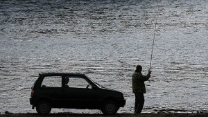 A man fishes near a car on the bank of the Mana river in the Siberian Taiga district near the village of Mansky, some 40 km (25 miles) southeast of Krasnoyarsk, May 2, 2011.  REUTERS/Ilya Naymushin  (RUSSIA - Tags: SOCIETY)