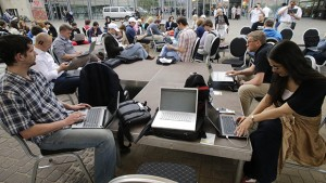 "People use their laptops during ""Working everywhere"" event in Riga May 31, 2013. More than 150 activists with laptops and wi-fi access attended event to demonstrate the benefits of flexible working style and possibly set a new Guinness world record for ""Most people who work in a specific place outside the office"". REUTERS/Ints Kalnins (LATVIA - Tags: SOCIETY)"