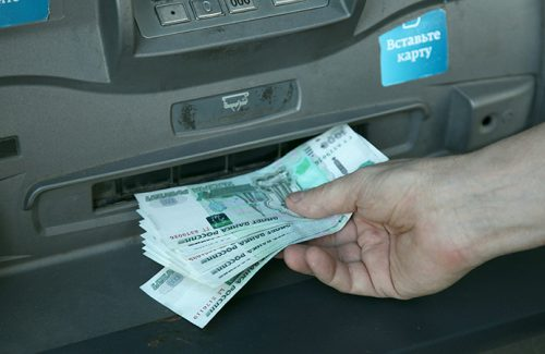 Man receives cash from an ATM of Sberbank of Russia.